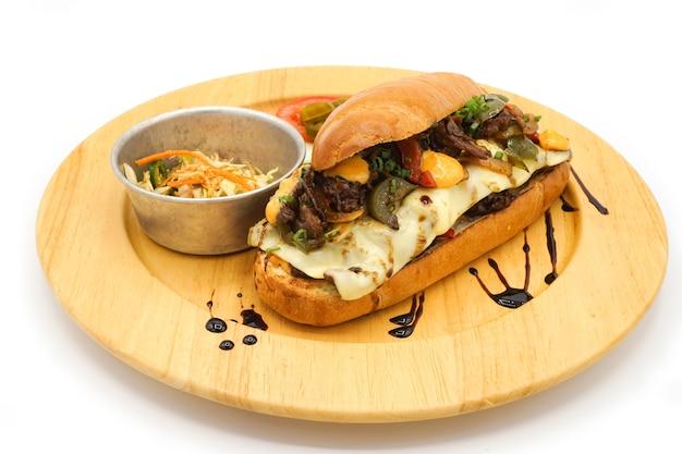 한미 핫도그 조식 스타일에 브리프 포크 치즈와 야채를 원형 우드 플레이트에 적용했습니다.