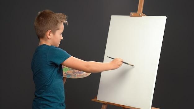 페인트가있는 팔레트를 들고 캔버스에 획을 적용합니다. 파란색 티셔츠를 입은 10 세 소년이 캔버스가있는 이젤 벽에 정면을 바라 봅니다.
