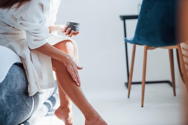 Наносит крем на стопы. обрезанное фото женщины в белой одежде, которая сидит на кровати в комнате. хорошее освещение.
