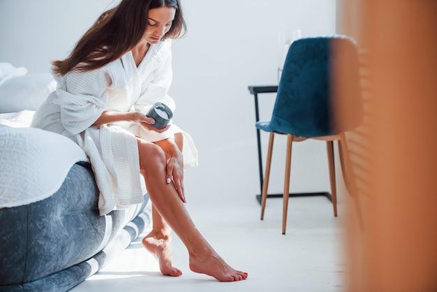 Наносит крем на стопы. портрет красивой брюнетки в белой одежде, которая сидит на кровати в комнате. хорошее освещение.