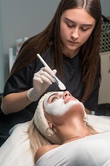 ビューティーサロンで顔にマスクをかける。美容師と若返りと保湿の手順。
