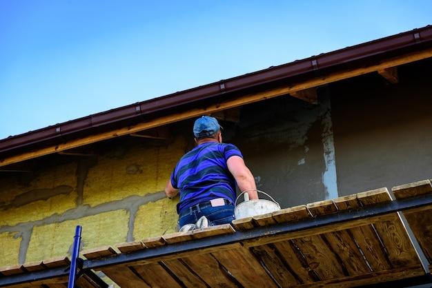 Нанесение слоя строительного клея на утепленную стену для покрытия стеклопластиковой арматурной сетки на минеральной вате.