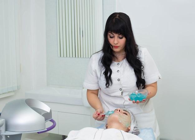 Нанесение косметического геля на лицо пациента. подготовка к процедуре эпиляции lazne. нанесение косметики на кожу.