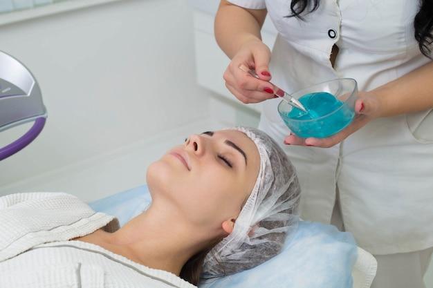 顔の患者に化粧用ジェルを塗る。ラズネ脱毛手順に直面する準備をしています。肌に化粧品を塗る。