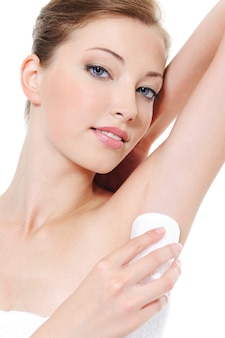 Applying cream deodorant on the armpit by young woman