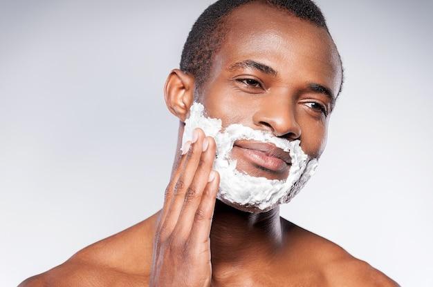Нанесите крем на лицо. африканский красавец без рубашки бреет лицо и смотрит в камеру, стоя на сером фоне