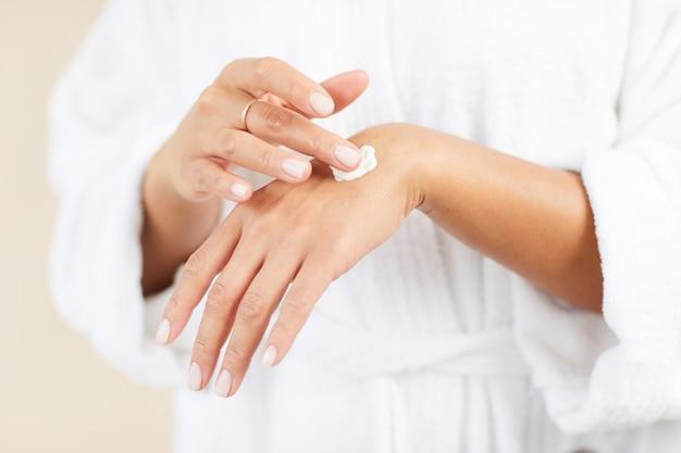 Применяя крем для рук крупным планом