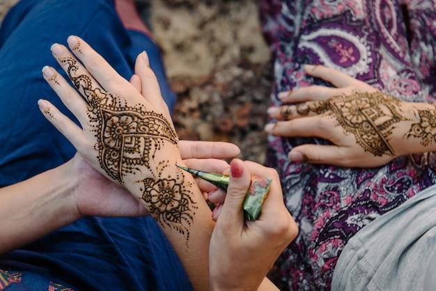 Нанесение татуировки хной на руки женщины. менди - традиционное индийское декоративное искусство. крупный план, вид сверху