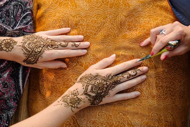 女性の手にヘナタトゥーを適用する