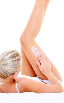 Applicazione della crema idratante sulle gambe da parte della giovane donna sdraiata sul letto
