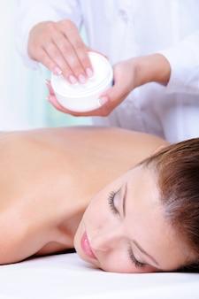 Applicazione di crema idratante per il massaggio alla schiena dell'estetista - fondo colorato