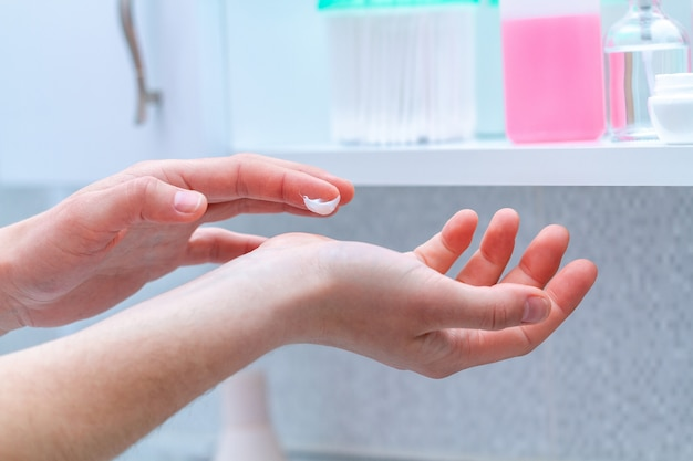 Applying moisturizing and nourishing hand cream for dry skin in bathroom at home. skin care, nutrition