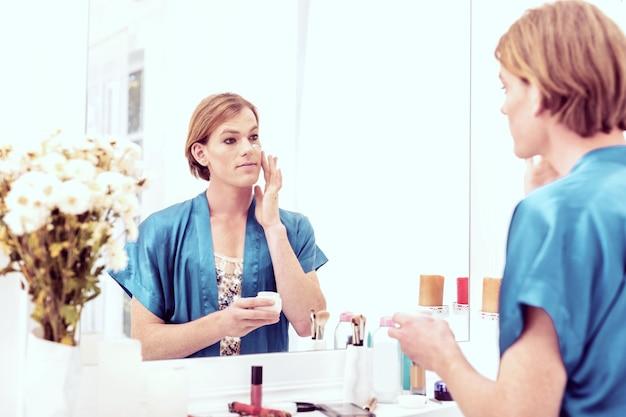 ナイトクリームを塗る。鏡に向かっていて、スキンケアで顔を覆っている格好良い若いトランスジェンダー