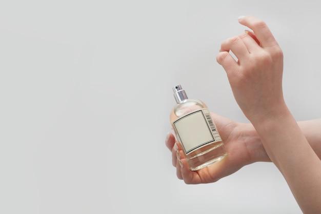 白い壁の手首に香水を塗ると、女性の手が一方の手首に他方の手で触れます。女性の香水のコンセプトです。