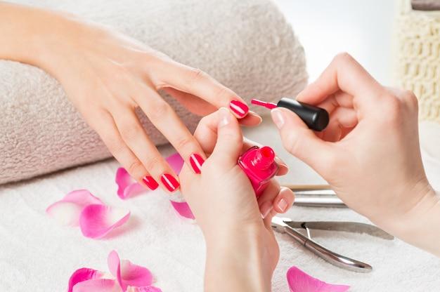 Applying pink nail polish