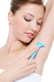 Applying razor to the shaving armpit by beautiful young girl