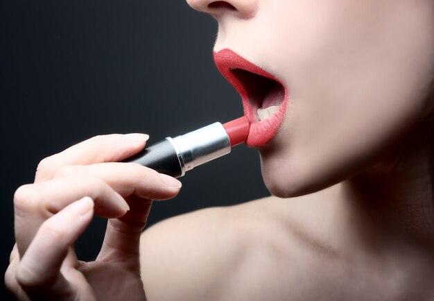 Applying a red lipstick