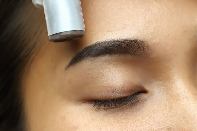 Applying tottoo microblading permanent make up to eyebrown