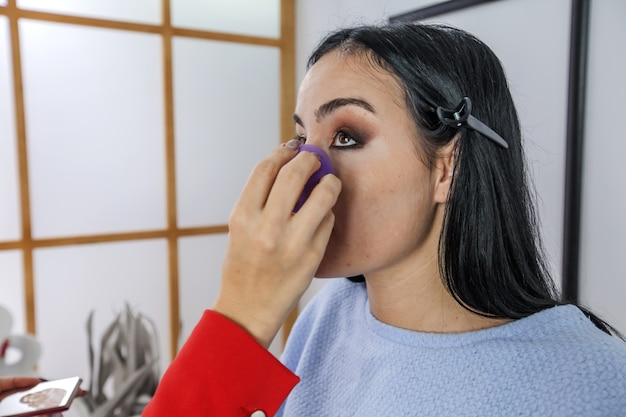 A applying transparent powder on the part of her face under her eyes