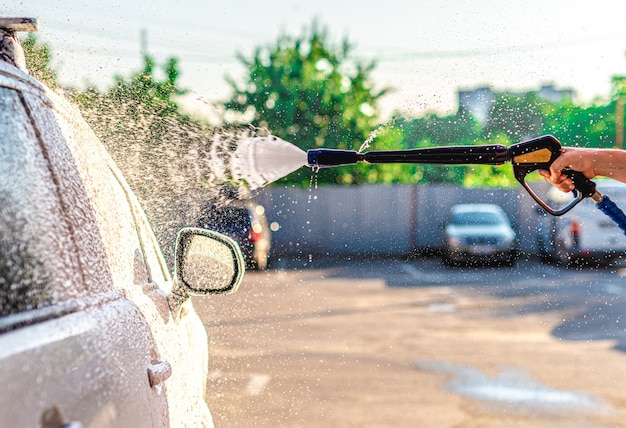Applying washing foam on car at car wash station
