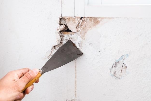 こてで壁のひびに白いセメントを塗る