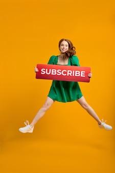 구독 버튼으로 콘텐츠를 감상하세요. 소셜 미디어 아이콘처럼 빨간 머리 여성이 들고 흥미로운 블로그, 인기 있는 포럼을 구독하기 위해 서명합니다. 노란색 배경에 고립 된 실내 스튜디오 촬영