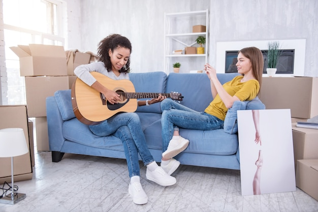 Ценить талант. очаровательная молодая девушка сидит на диване рядом со своей лучшей подругой и снимает, как она играет на гитаре по телефону
