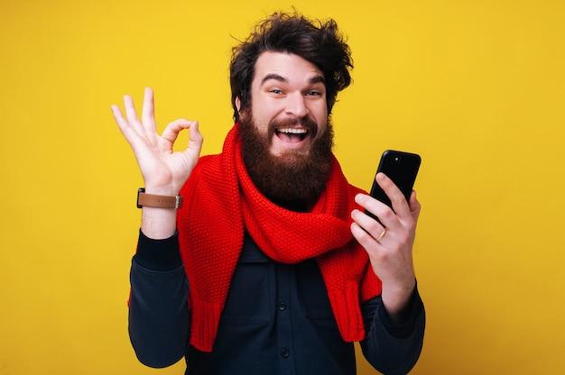 승인했습니다! 노란색 외진 배경 위에 서서 휴대폰을 들고 확인 표시를 하고 있는 쾌활한 수염 난 남자의 사진