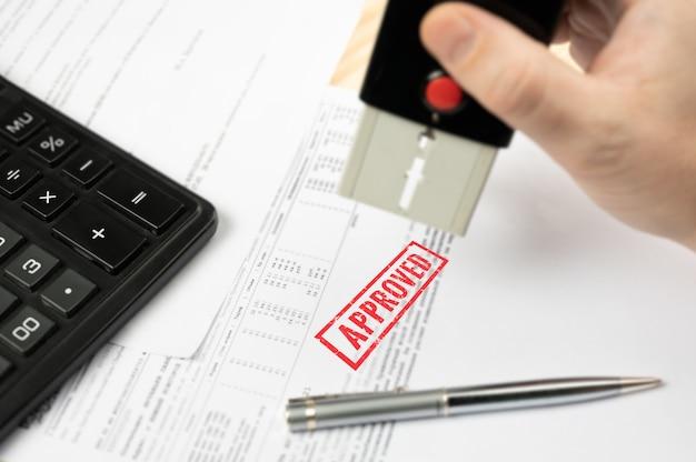 승인 된 스탬프입니다. 승인 된 계약 양식에 스탬핑하는 비지니스의 손 클로즈업.
