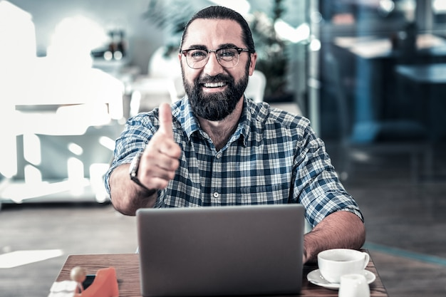 作業を承認します。彼の従業員の仕事を承認する眼鏡をかけているひげを生やした暗い目のビジネスマン