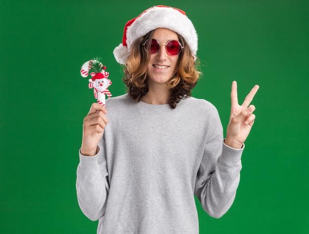クリスマスのサンタの帽子と赤い眼鏡を身に着けている幸せな男は、緑の背景の上に立っているvサインを元気に見せて笑っているカメラを見てクリスマスキャンディケインを保持しています
