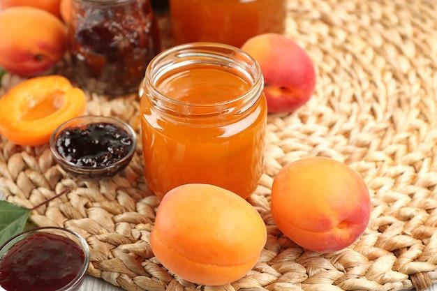 籐のマットの上に熟したジューシーなフルーツとアプリコットとベリーのジャム