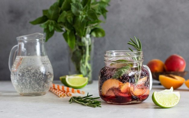 Apricot and black currant lemonade in glass with fresh apricot, rosemary, mint and lime.