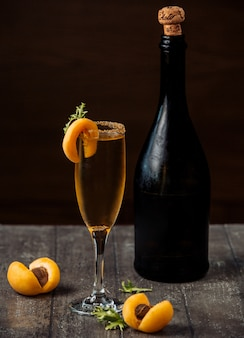 Apricot champagne in champagne glass garnished with apricots on wood counter