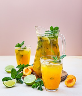 Apricot cocktail or ice tea with fresh mint, lime and apricots. summer refreshing cold drink.