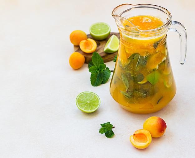 Абрикосовый коктейль или ледяной чай со свежей мятой, лаймом и абрикосами. летний освежающий холодный напиток.