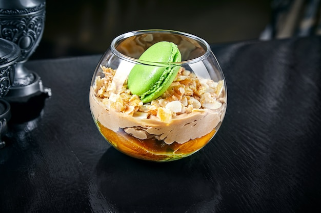 Apricot dessert with macaroon in a jar. pudding with apricot and almond. close up sweet food background with copy space. dessert cream mousse. homemade yogurt. apricot jam and cream