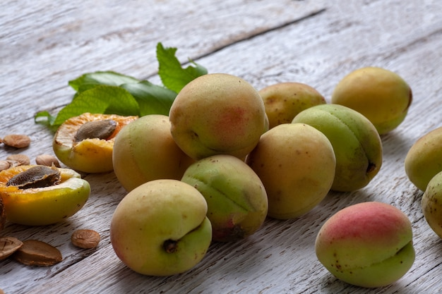 살구 과일. 흰색 나무 배경에 신선한 유기농 살구. 베가 음식.