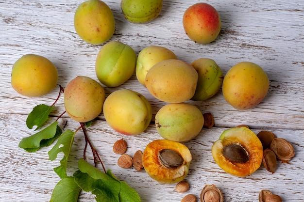 살구 열매. 흰색 나무 테이블에 신선한 유기농 살구입니다. 베가 음식.