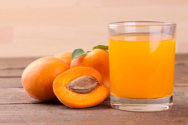 갈색 나무 배경에 있는 신선한 살구 옆에 있는 유리 컵에 있는 살구 주스