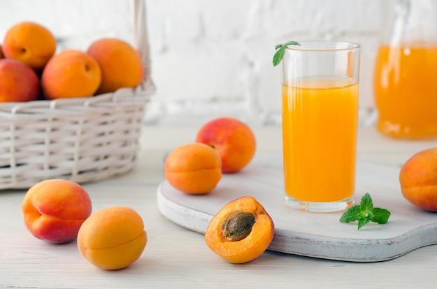 Сок абрикоса в стекле и графине и спелых абрикосах в корзине на фоне белой кирпичной стены. крупный план.