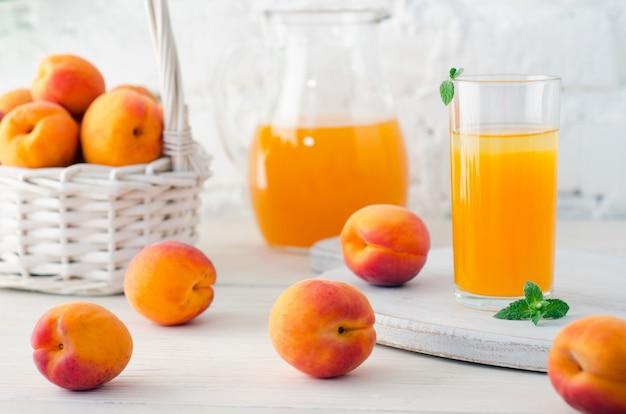 Абрикосовый сок в стекле и графине со спелыми абрикосами на деревянном столе на фоне белой кирпичной стены. крупный план.