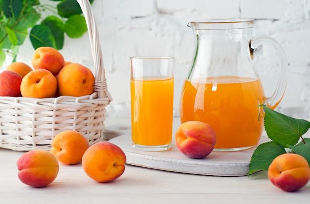 Абрикосовый сок в стекле и графине со спелыми абрикосами на деревянном столе на фоне белой кирпичной стены с зелеными листьями.
