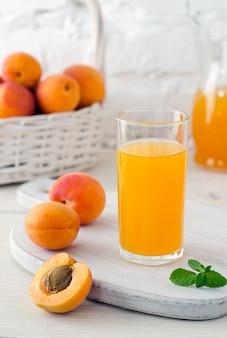Абрикосовый сок в стекле на кухонной доске и спелые абрикосы в корзине на фоне белой кирпичной стены. крупный план.