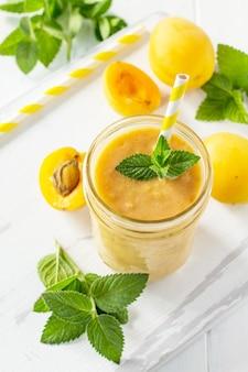 白い木製の背景にアプリコットミルクセーキまたはスムージー健康的なジューシーなビタミン飲料