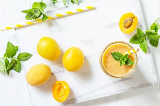 アプリコットミルクシェイクまたは白い木製の背景にスムージー健康的なジューシーなビタミン飲料
