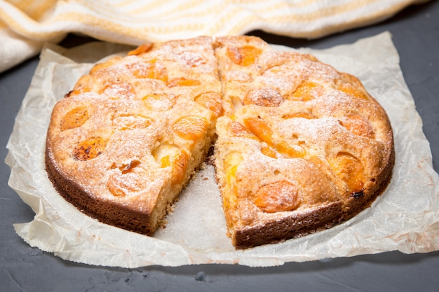Apricot pie on the baking paper with ripe apricots
