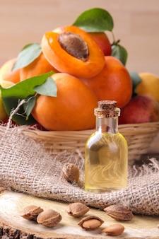 Масло косточек абрикоса на деревянной подставке рядом со свежими абрикосами на коричневом деревянном столе