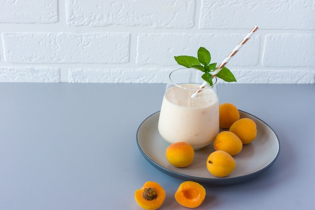 Apricot smoothie or yogurt and ripe apricots on a table. delicious milk drink with ripe apricots.
