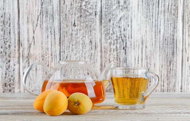 Apricot tea in teapot and glass mug with apricots side view on a wooden table